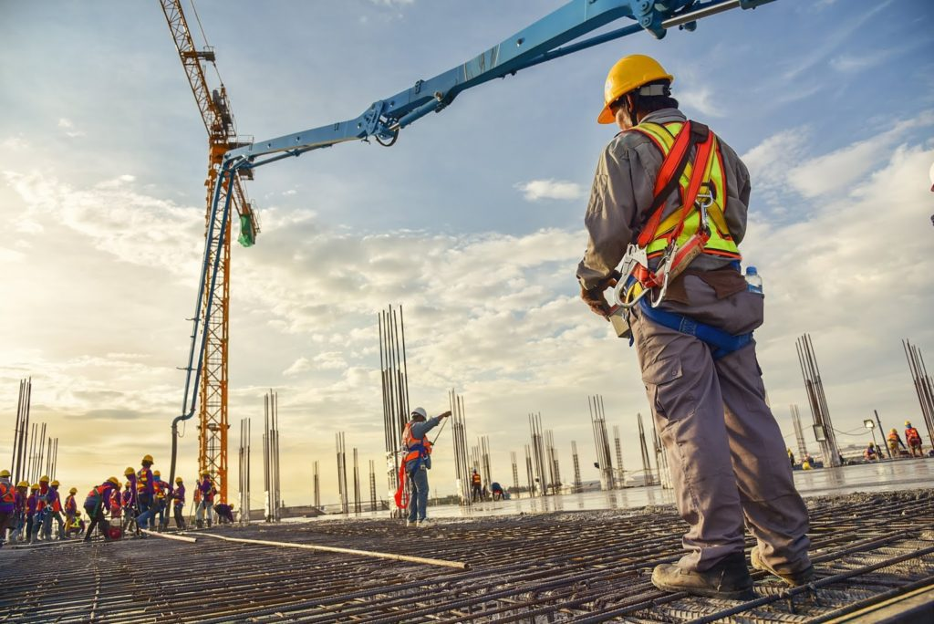 Construction worker controlling a pouring concrete pump on a construction site with the sunset in the background